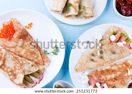Pancake day, mardi gras, maslenitsa background. Thin rolled pancakes, crepes with red caviar and salmon, pickled cucumbers and bacon. Traditional Russian dish. - stock photo
