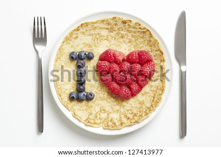Pancake on plate with love heart shape on white table - stock photo