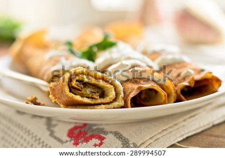 Pancake rolls with mushrooms and yogurt dip - stock photo