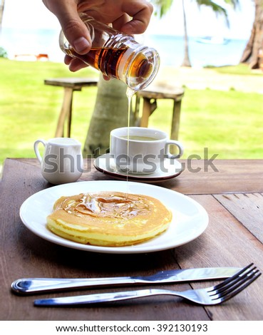 Pancake syrup is slowing flowing down on the freshly backed pancake. Bottle with syrup is held by the male hand. Scene is taken outdoors, at the terrace with tropical garden on the background.  - stock photo
