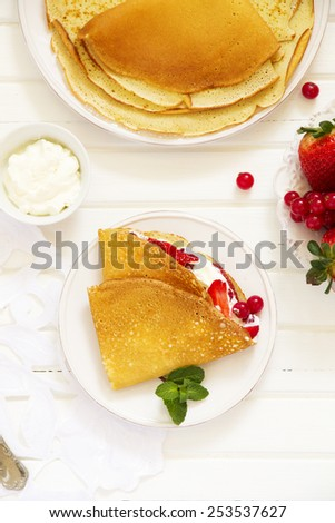 Pancakes filled with whipped cream and berries. - stock photo