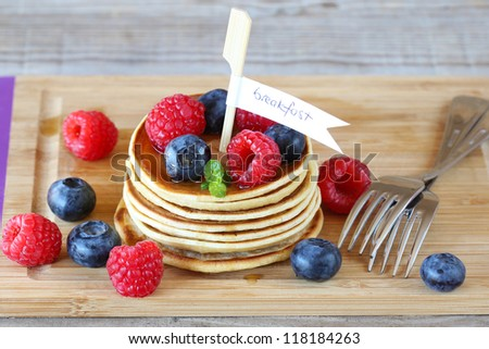 Pancakes for breakfast with berries and maple syrup - stock photo