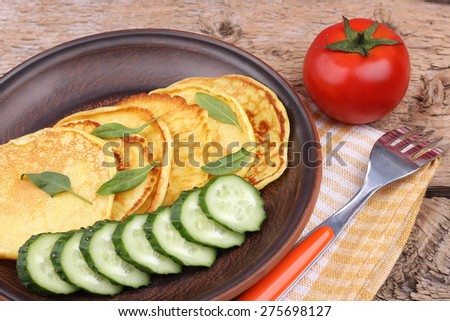 Pancakes on the plate. Cooking. Vegetables and pancakes. Dough. Tomato, cucumber and pancakes. Thin pancakes. Breakfast. Fork on the napkin. Plate and fork. Pancakes with greens and vegetables.  - stock photo