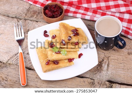 Pancakes on the plate. Cup of coffee with milk, sweet pancakes and mint. The plate of food on the table. Breakfast, lunch. Classic Breakfast. Food and beverage. Delicious thin pancakes. - stock photo