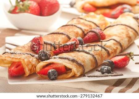 Pancakes served with strawberries, blueberries and chocolate on plate. Shallow dof - stock photo