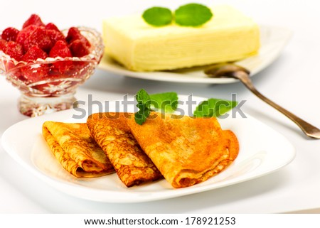 Pancakes, strawberries in a vase and briquette butter - stock photo