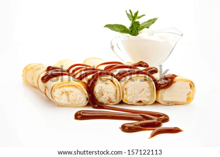 pancakes stuffed with cottage cheese with dried apricots, covered with caramel, cream, white background - stock photo