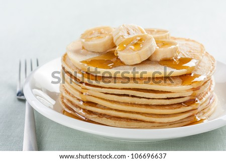 pancakes with banana and syrup on white plate - stock photo