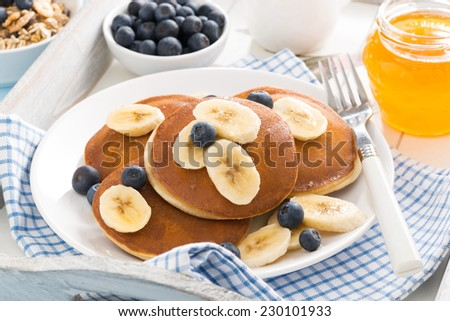 pancakes with banana, honey and blueberries for breakfast on a tray, horizontal - stock photo