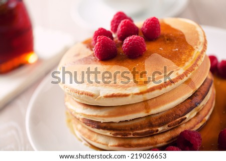 Pancakes with berries and maple syrup - stock photo