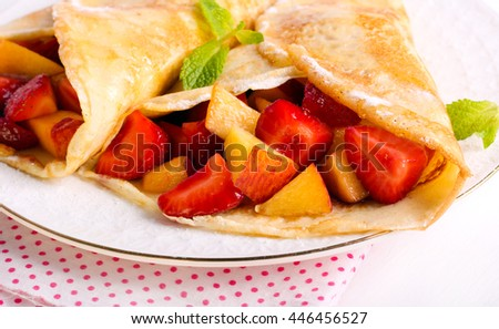Pancakes with berry and fruit filling, on  plate - stock photo