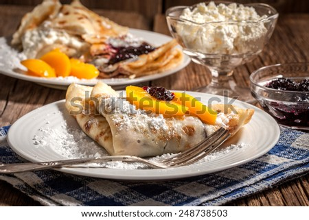 Pancakes with blackberry jam and cheese on a wooden background. - stock photo