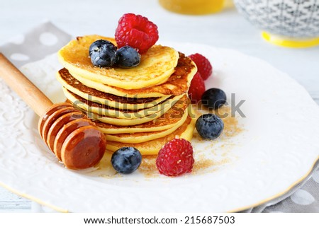 Pancakes with blueberries and raspberries with honey on  plate, side view - stock photo