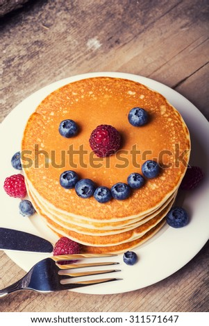 Pancakes with blueberries , honey & raspberry on wood background . Smile - stock photo