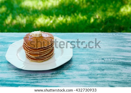 Pancakes with butter and honey on white plate on blue wooden background in garden or on nature background. Stack of wheat golden pancakes or pancake cake, closeup. - stock photo