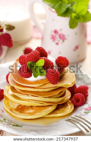 Pancakes with fresh raspberries and creamy soft cheese. - stock photo
