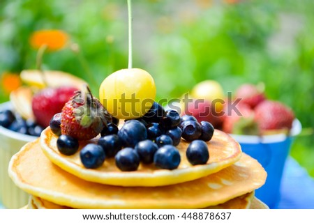 Pancakes with fresh raspberries, strawberries, cherries, blueberries on blue wooden background - stock photo
