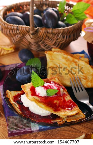 pancakes with homemade plum confiture and whipped cream on autumn rural table - stock photo
