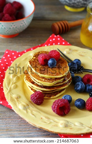 Pancakes with honey and berries, side view - stock photo