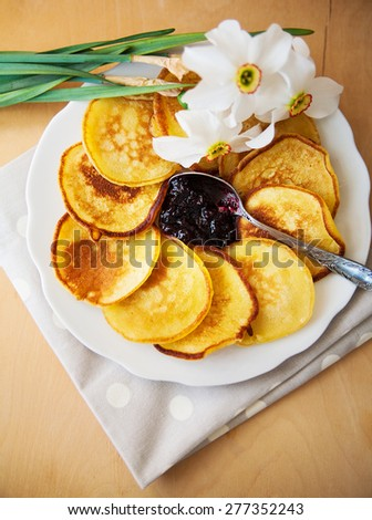 Pancakes with jam and spoon on a plate and white daffodils on wooden background - stock photo