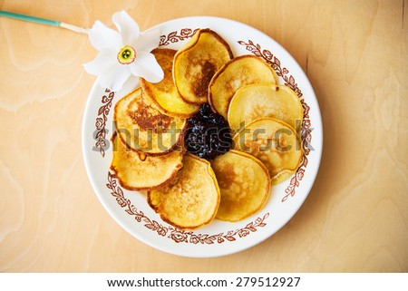 Pancakes with jam on a plate and white daffodils on wooden background. Top view - stock photo