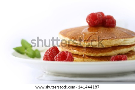 Pancakes with raspberry and honey on top - stock photo