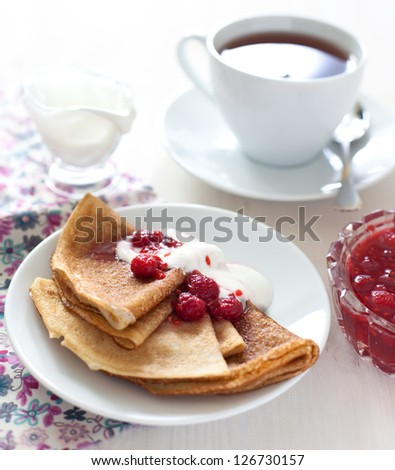 Pancakes with raspberry jam and cream on wooden background - stock photo