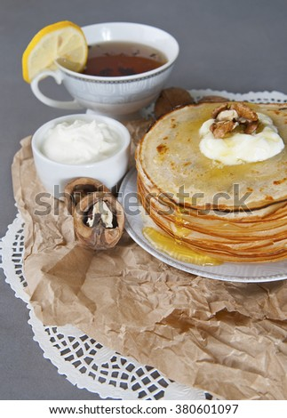 Pancakes with sour cream and honey, decorated with walnut.Studio shot on a gray stone countertop. - stock photo