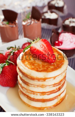 Pancakes with strawberries and candies on background - stock photo