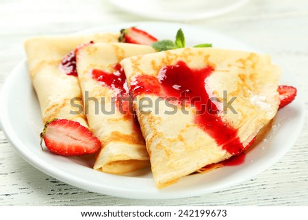 Pancakes with strawberry on plate on white wooden background - stock photo