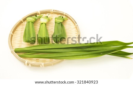 Pandan leaf is also know as screw pine.  The leaves have a strong sweet fragrance hence often used to scent and flavor food.  The long green leaves are tied into a knot for easy removal after cooking. - stock photo