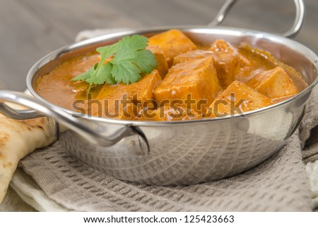 Paneer Makhani or Shahi Paneer (Paneer Butter Masala) - Indian curd cheese curry in a balti dish, served with naan bread and garnished with coriander leaves. - stock photo