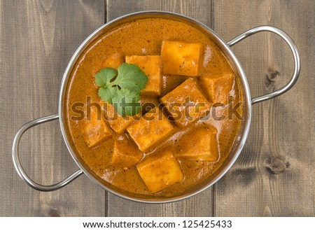Paneer Makhani or Shahi Paneer (Paneer Butter Masala) - Indian curd cheese curry served in a balti dish and garnished with coriander leaves. Shot from above (overhead). - stock photo