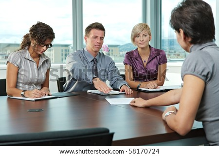 Panel of business people sitting at table in meeting room conducting job interview. Applicant showing documents. - stock photo