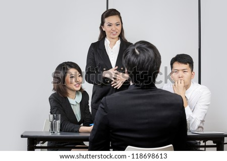 Panel of Chinese colleagues from hr department interview a male applicant. - stock photo