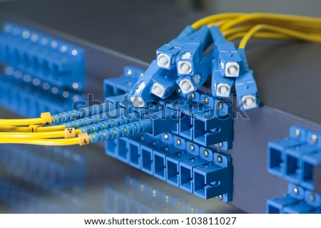 Panel of Fiber network switch with some yellow network cables - stock photo
