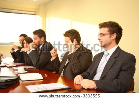 Panel of four businessmen and one businesswoman, all with serious expressions. - stock photo