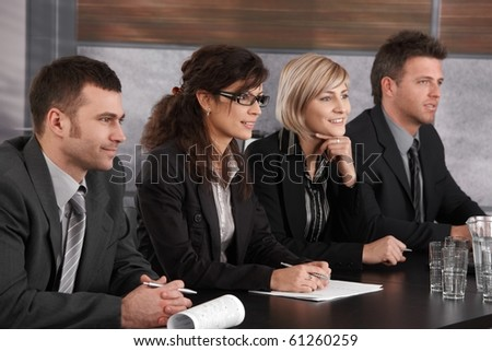 Panel of friendly businesspeople sitting at meeting table conducting job interview. ? - stock photo