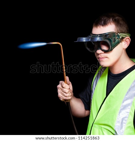 Panelbeater in safety goggles holding the nozzle of an oxyacetylene torch in preparation for welding repaired bodywork on a motor car - stock photo