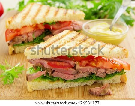 Panini closeup with roast beef and salad. - stock photo