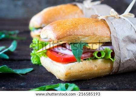 Panini sandwich stuffed with ham and cheese on wooden background,selective focus - stock photo