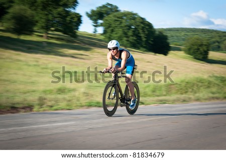 Panned shot of bicyclist in biking gear riding fast. - stock photo