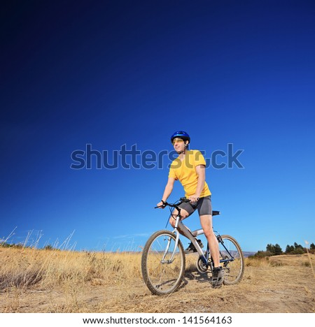 Panning shot of a bicycle rider riding a mountain bike outdoors on a sunny day against a cloudless blue sky - stock photo