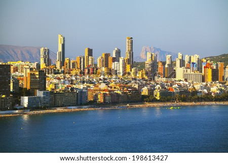Panorama coast with people relaxing on urban background of houses and hotels (View of the Benidorm, Spain) - stock photo