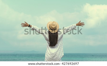 Panorama Happy young girl feeling free with arms open outdoors. Smile Freedom and happiness woman on beach. She is enjoying serene ocean nature during travel holidays vacation outdoors. asian beauty - stock photo