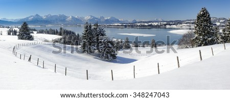 panorama landscape in Bavaria with alps mountains and lake Forggensee - stock photo