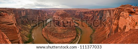 Panorama landscape of the Horseshoe Bend Colorado river after rainstorm. Dramatic stormy cloudy sky. Grand Canyon, Arizona, USA. Tourists making pictures. Natural wonder. - stock photo