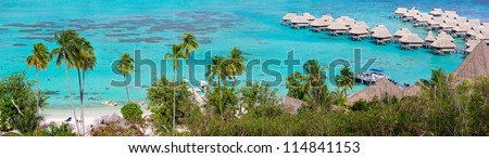 Panorama of a beautiful coast and over water bungalows at Moorea island - stock photo