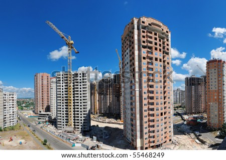 Panorama of a building site with a lot of residential high-rises under construction against beautiful summer sky. - stock photo