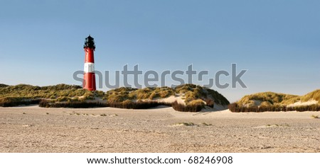 Panorama of a german lighthouse at the beach - stock photo